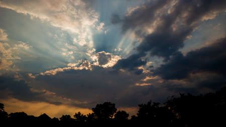 The sun covered by a storm cloud and the sun's rays against the background of the sky 写真素材