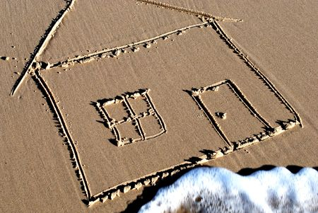 Conceptual picture of a house drawn in the sand with a wave washing over it