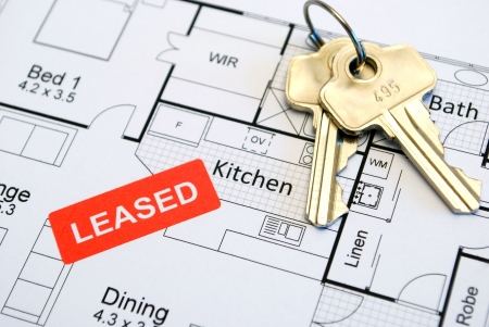 close up of house plans with leased sign and keys photo