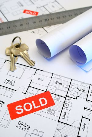 close up of rolled house plans with red sold sign and keys