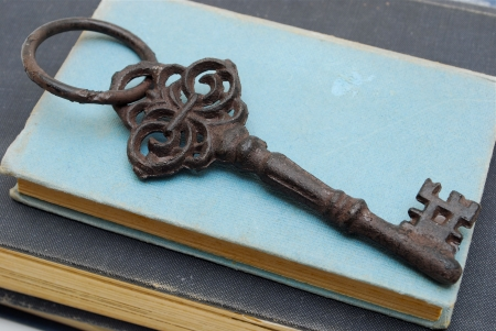 key to success: old antique key on blue  books Stock Photo