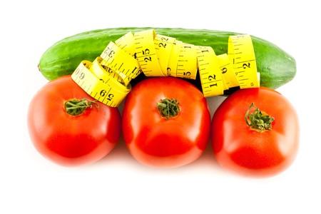 bureta: Medir con tomate y pepino sobre un fondo blanco  Foto de archivo
