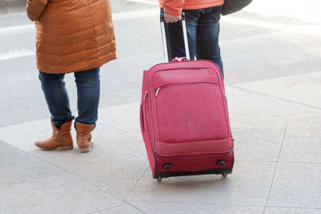 jetsetter: legs of the person rolling a tourist bag on wheels in summer day