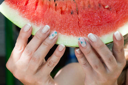 the girls hands holding a piece of beautiful ripe watermelon