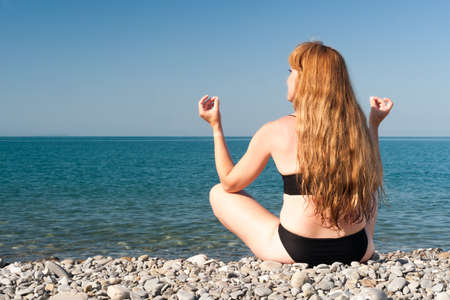 the girl sits on the seashore in the weakening pose in clear summer day