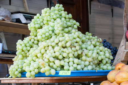 juicy green grapes on a counter of shop in summer day