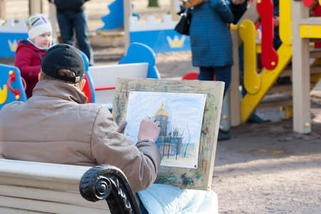 ST. PETERSBURG, RUSSIA - MARCH 27 2016: the artist draws the city from nature. In Russia, many people are fond of painting