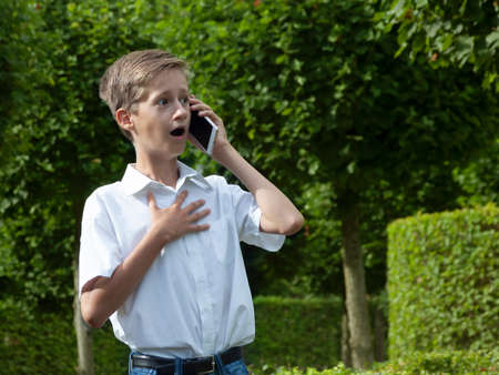The boy emotionally speaks in the park by phone on summer day
