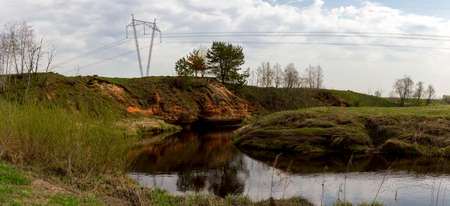 panorama of the twisting abrupt coast of the small river with power lines in summer cloudy day