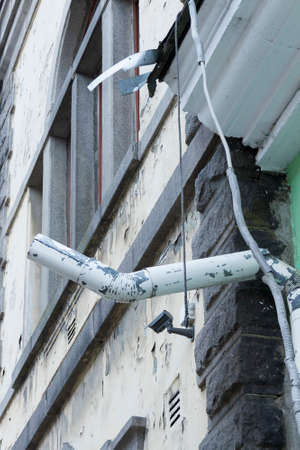 half-ruined pipe of a drain on the building in the city of Vyborg, Russia Imagens