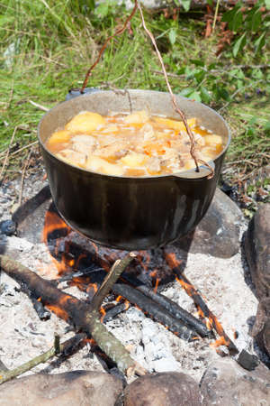 tourist kettle with the cooked food over the burning fire in summer day Banco de Imagens