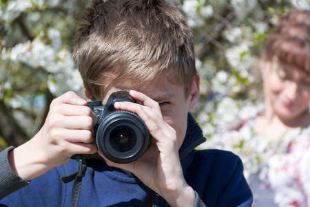 the son photographs mother against the background of a bird cherry in summer day