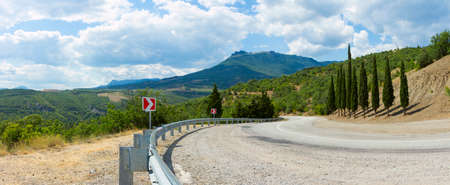 panorama of the twisting road in mountains in clear summer day