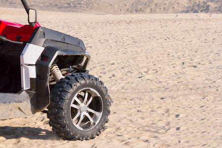 the ATV goes on desert sands to clear sunny day