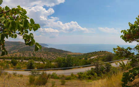 panorama of the twisting road in mountains on the coast in clear summer day Banco de Imagens