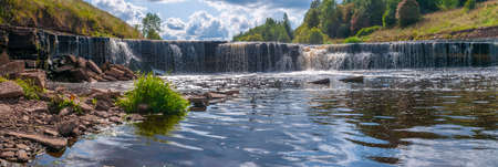 Panorama of waterfall on mountain river on clear summer day