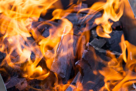 Burning coals in mangal with bright flame, background image