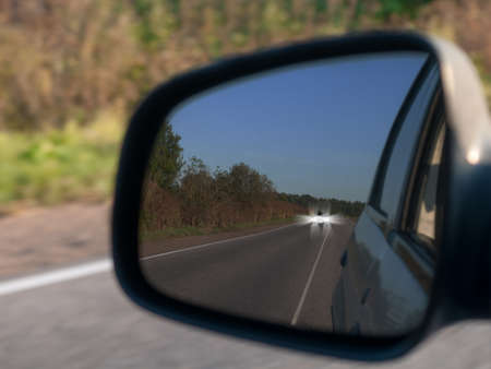 rear-view mirror of the car in which the car overtaking through the continuous line is reflected