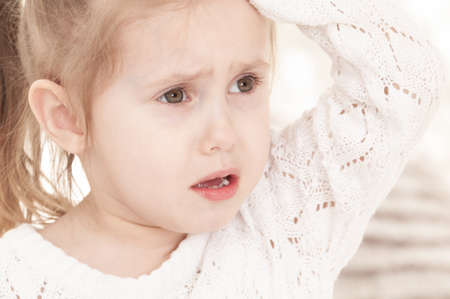 close-up portrait of a three-year-old whining girl in a light dress