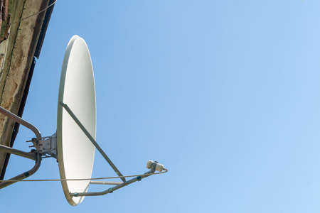 the satellite antenna installed on a house facade in clear day