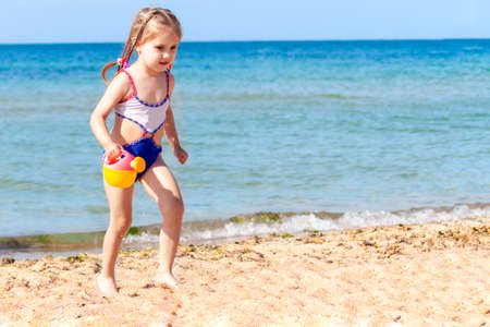 little beautiful girl walks along the beach by the sea on a clear summer day