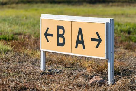 Yellow and black airport direction signs pointing taxiways. Stock Photo