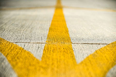 Yellow direction strips closeup on an airfield runway.