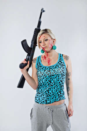 Dangerous young woman holding automatic rifle photo