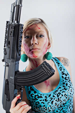 sweatsuit: Close up of a dangerous young woman covered in blood, holding automatic rifle
