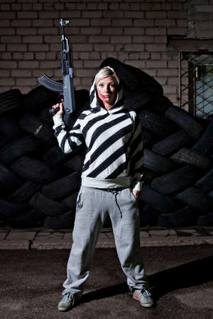 automate: Dangerous young woman holding automatic rifle