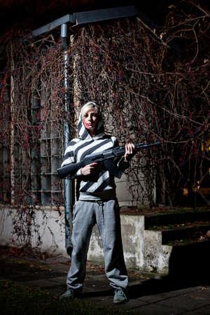 sweatsuit: Dangerous young woman holding automatic rifle