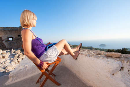 lanscape: Young woman enjoys the view of a lanscape and sea Stock Photo
