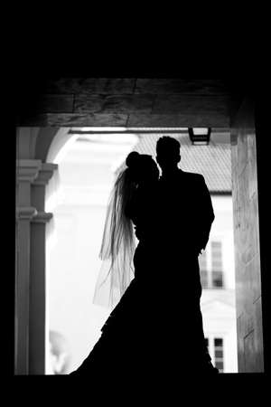 Dark silhouette of groom and bride