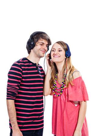 Happy young couple listening to a music isolated on a white background photo