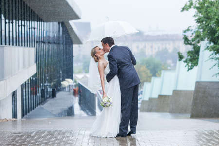 couple in rain: Rain pours on a wedding day Stock Photo