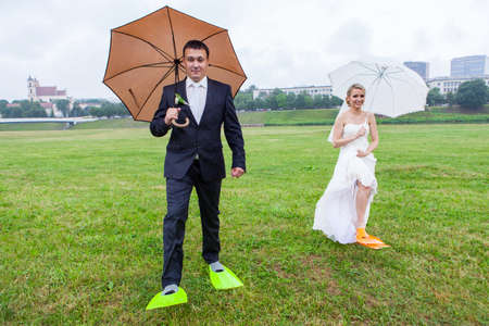 couple in rain: Couple wear flippers on a rainy wedding day