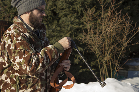 Man in winter forest reloads pneumatic weapons. Hunter dressed in camouflage with pneumatic gun, rifle The man in the white winter forest loads long arms. Stock Photo