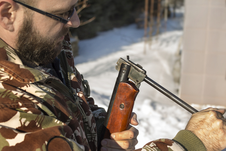 Hunter hunting reload firearms in the winter scenery.