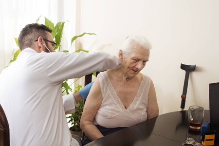 geriatrician: Doctor examining an old woman with a stethoscope in a doctors office. Medical examination with a stethoscope. Geriatrician doctor examining lungs.