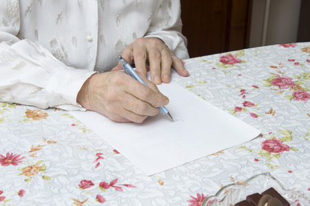 Hands of the old woman who writes handwritten testament on a piece of paper Stock Photo