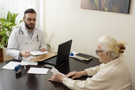 geriatrician: The geriatrician doctor with a patient. Receives documents from the patient.Old woman at the doctor geriatrician.geriatrician doctor with a patient in his office. Stock Photo