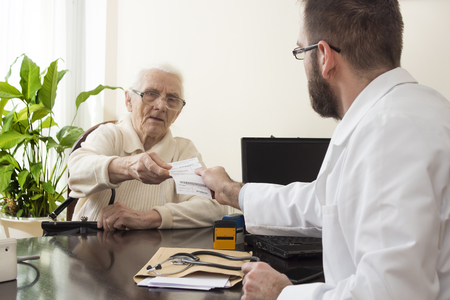 geriatrician: The doctor gives the patient a prescription. geriatrician doctor with a patient in his office. Old woman at the doctor geriatrician.