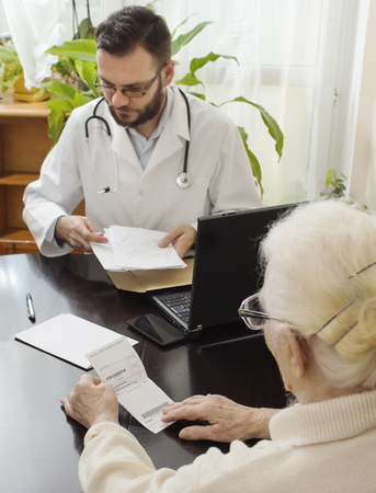 doctors office. A doctor takes a patient. The patient, an old woman reading a record on the prescription issued by a doctor.Old woman at the doctor geriatriciangeriatrician doctor with a patient in his office. Stock Photo