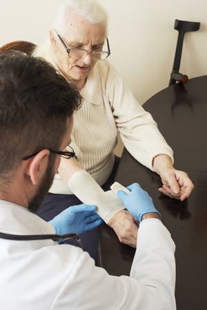 doctor s smock: Old woman at the doctor. The doctor Provides the patients hand. Bandage the hand by a doctor. Stock Photo
