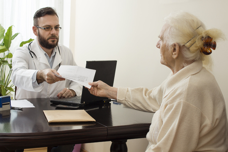 geriatrician: geriatrician doctor with a patient in his office.The geriatrician doctor with a patient. Receives documents from the patient.Old woman at the doctor geriatrician.