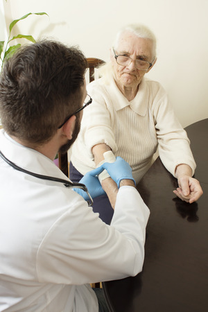 doctor s smock: A private doctors office. Doctor examining an old womans hand. Old woman at the doctor. The doctor Provides the patients hand. Bandage the hand by a doctor. Stock Photo
