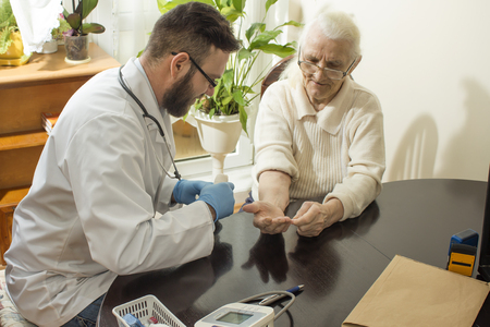 geriatrician: A private doctors office. Doctor examining an old womans hand. Old woman at the doctor. The doctor Provides the patients hand. Bandage the hand by a doctor. Stock Photo