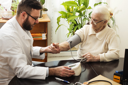 geriatrician: A private doctors office. Geriatrician doctor takes the patient and measure her blood pressure.