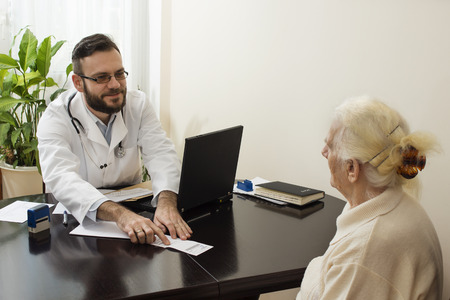geriatrician: A doctor at work. He shows a finger and translates the patient record on the prescription.