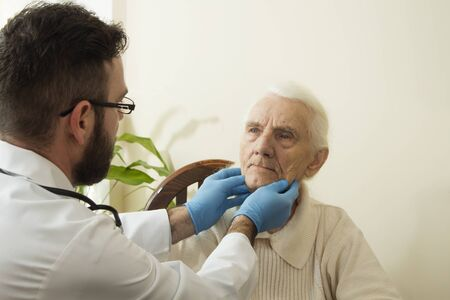 moles: The doctor examines the lymph nodes on the neck of an old woman.